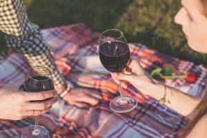 Zwei Weingläser mit Rotwein gefüllt. Sommer Sonne und Picknickdecke