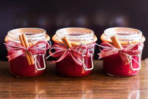 drei Einmachgläser mit roter Marmelade und verziert mit Zimtstange, weingelee